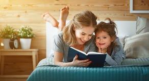 Livre de lecture heureux de mère et de fille de famille dans le lit Photographie stock