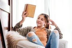 Livre de lecture de jeune femme à la maison avec Smiley Face heureux et vrai images libres de droits