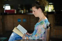 Livre de lecture de jeune femme Images stock