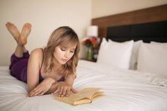 Livre de lecture de jeune femme dans la chambre à coucher image stock