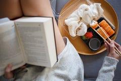 Livre de lecture de jeune femme et sushi de consommation photographie stock libre de droits