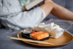 Livre de lecture de jeune femme et sushi de consommation photos stock