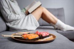 Livre de lecture de jeune femme et sushi de consommation photo libre de droits