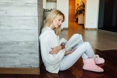 Livre de lecture de jeune femme sur le plancher près du mur léger photographie stock libre de droits
