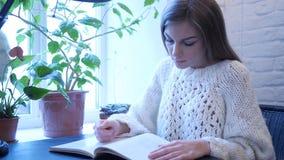 Livre de lecture de jeune femme tout en se reposant dans le bureau images stock