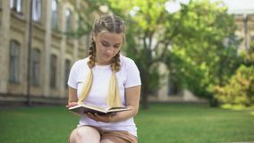 Livre de lecture de l'adolescence concentré de fille dans le jardin d'université, se préparant à l'essai banque de vidéos