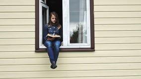 Livre de lecture de l'adolescence de fille se reposant dans une fenêtre clips vidéos