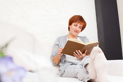 Livre de lecture mûr adulte de femme Photo stock