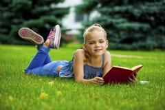 Livre de lecture mignon adorable de petite fille dehors sur l'herbe Photos stock