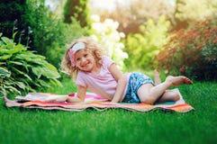 Livre de lecture mignon de fille d'enfant dans le jardin d'été extérieur Photographie stock libre de droits