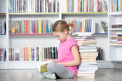 Livre de lecture mignon de fille dans la bibliothèque Photographie stock