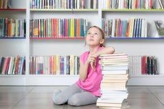 Livre de lecture mignon de fille dans la bibliothèque Photos libres de droits