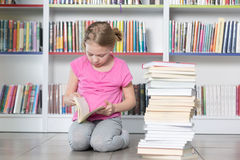 Livre de lecture mignon de fille dans la bibliothèque Photos stock