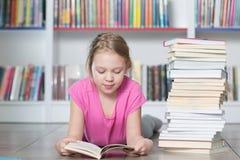 Livre de lecture mignon de fille dans la bibliothèque Photo stock