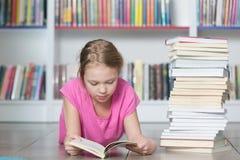 Livre de lecture mignon de fille dans la bibliothèque Image stock