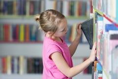 Livre de lecture mignon de fille dans la bibliothèque Photographie stock libre de droits