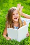 Livre de lecture mignon de petite fille dehors sur l'herbe Photographie stock libre de droits