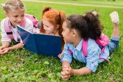 Livre de lecture multi-ethnique d'enfants sur l'herbe Images stock