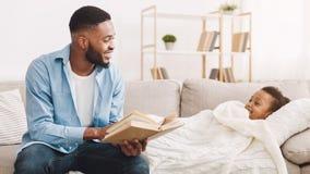 Livre de lecture de père d'afro-américain à la fille sur le sofa photo stock