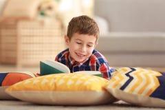 Livre de lecture de petit garçon sur le plancher avec des oreillers Photos libres de droits