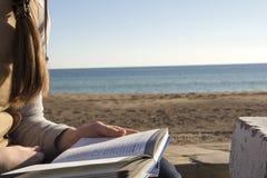 Livre de lecture près de bord de la mer Photographie stock libre de droits