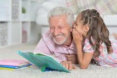 Livre de lecture première génération avec sa petite-fille Photographie stock libre de droits