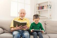 Livre de lecture première génération, petit-fils à l'aide du comprimé Photographie stock libre de droits