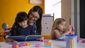 Livre de lecture de professeur et d'enfant dans le jardin d'enfants banque de vidéos