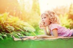 Livre de lecture rêveur de fille d'enfant dans le jardin d'été Photographie stock