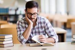 Livre de lecture sérieux d'étudiant masculin à la bibliothèque universitaire image libre de droits