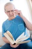 Livre de lecture songeur d'homme supérieur à la maison Photos libres de droits
