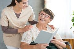 Livre de lecture de sourire de grand-maman Images libres de droits