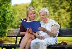 Livre de lecture supérieur de femme en parc Image stock