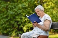 Livre de lecture supérieur de femme en parc Photographie stock libre de droits