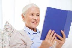 Livre de lecture supérieur de sourire heureux de femme à la maison Photo stock