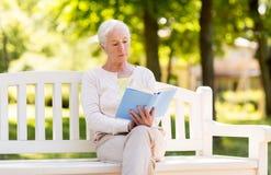 Livre de lecture supérieur de femme au parc d'été Images stock