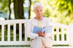 Livre de lecture supérieur de femme au parc d'été Photographie stock libre de droits