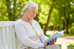 Livre de lecture supérieur heureux de femme au parc d'été Image libre de droits