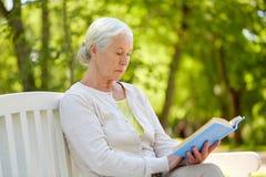 Livre de lecture supérieur heureux de femme au parc d'été Photographie stock