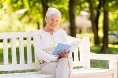 Livre de lecture supérieur heureux de femme au parc d'été Image stock