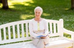 Livre de lecture supérieur heureux de femme au parc d'été Images stock