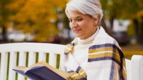 Livre de lecture supérieur heureux de femme au parc d'automne clips vidéos