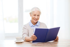 Livre de lecture supérieur de sourire heureux de femme à la maison Photos stock