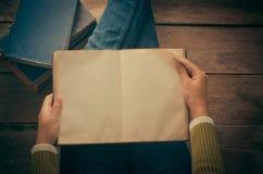 Livre de lecture sur le plancher en bois avec le livre - modifiez la tonalité le vintage photos stock