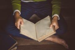 Livre de lecture sur le plancher en bois avec le livre - modifiez la tonalité le vintage photographie stock libre de droits