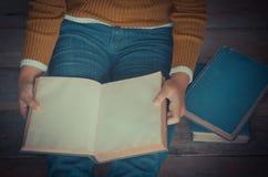 Livre de lecture sur le plancher en bois avec le livre - modifiez la tonalité le vintage image stock