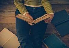 Livre de lecture sur le plancher en bois avec le livre - modifiez la tonalité le vintage photo stock