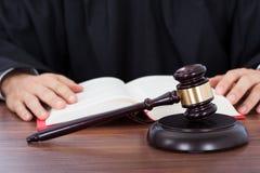 Livre de loi de lecture de juge au bureau Photos libres de droits