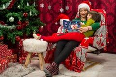 Livre de Noël de lecture de mère et de fils ensemble photographie stock libre de droits