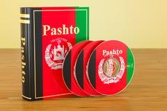 Livre de Pashto avec le drapeau de l'Afghanistan et des disques CD sur l'en bois Photos stock